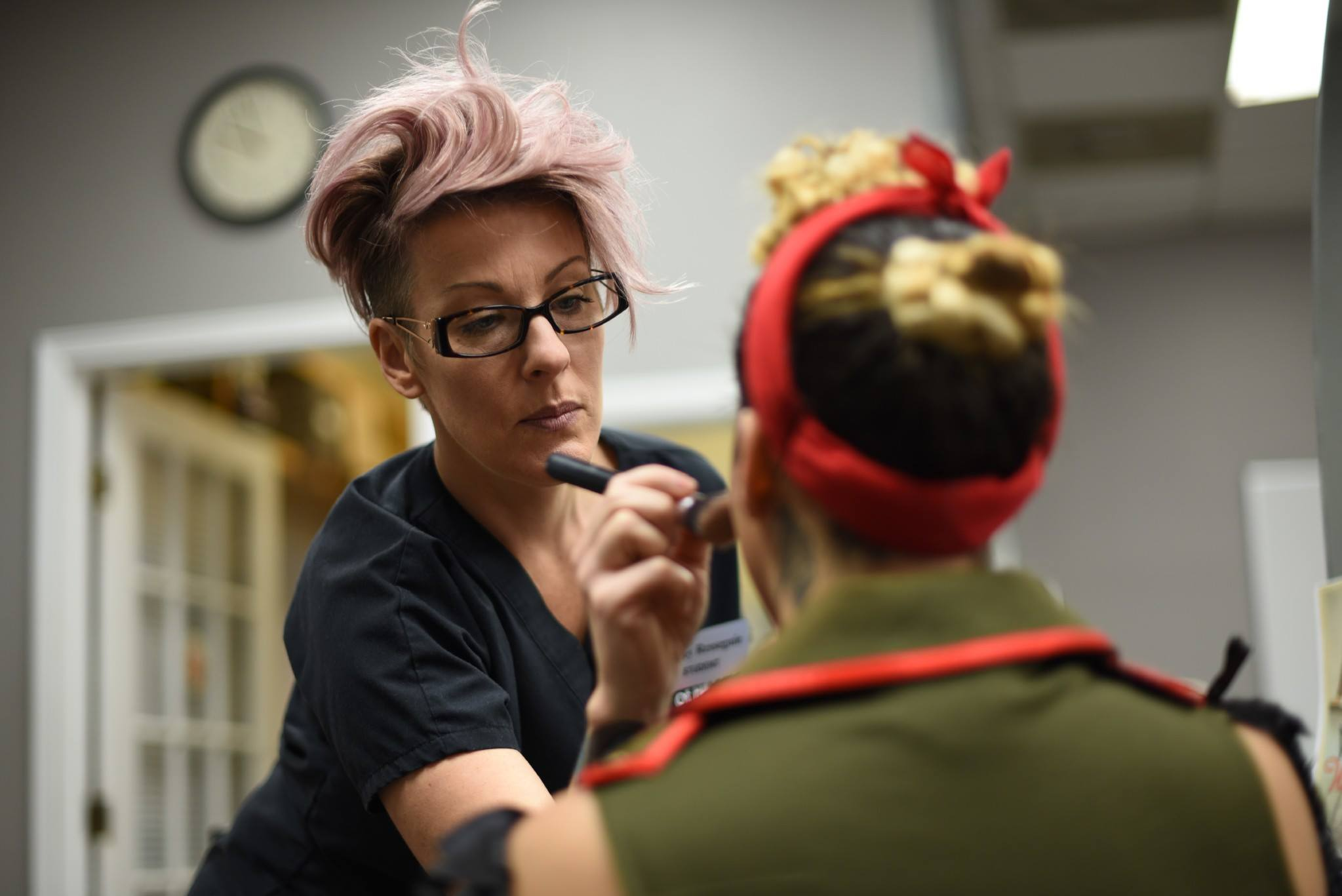 Closeup shot of pink haired woman applying makeup to another girl