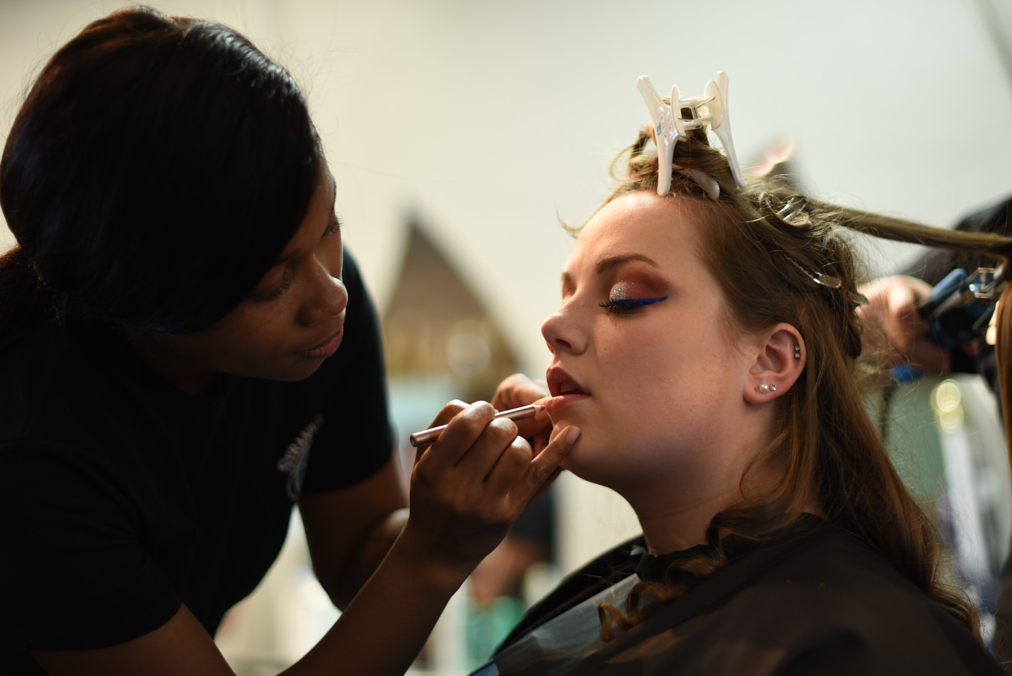 Girl applying lipstick on another girl