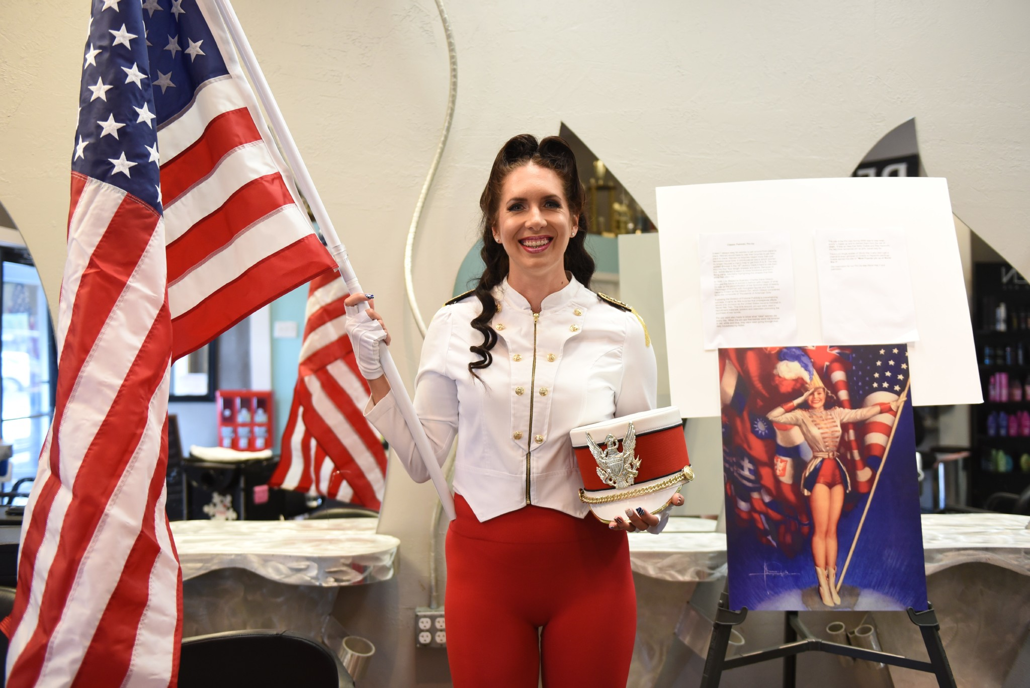 Woman dressed in white and red sailor outfit smiling while holding an American flag