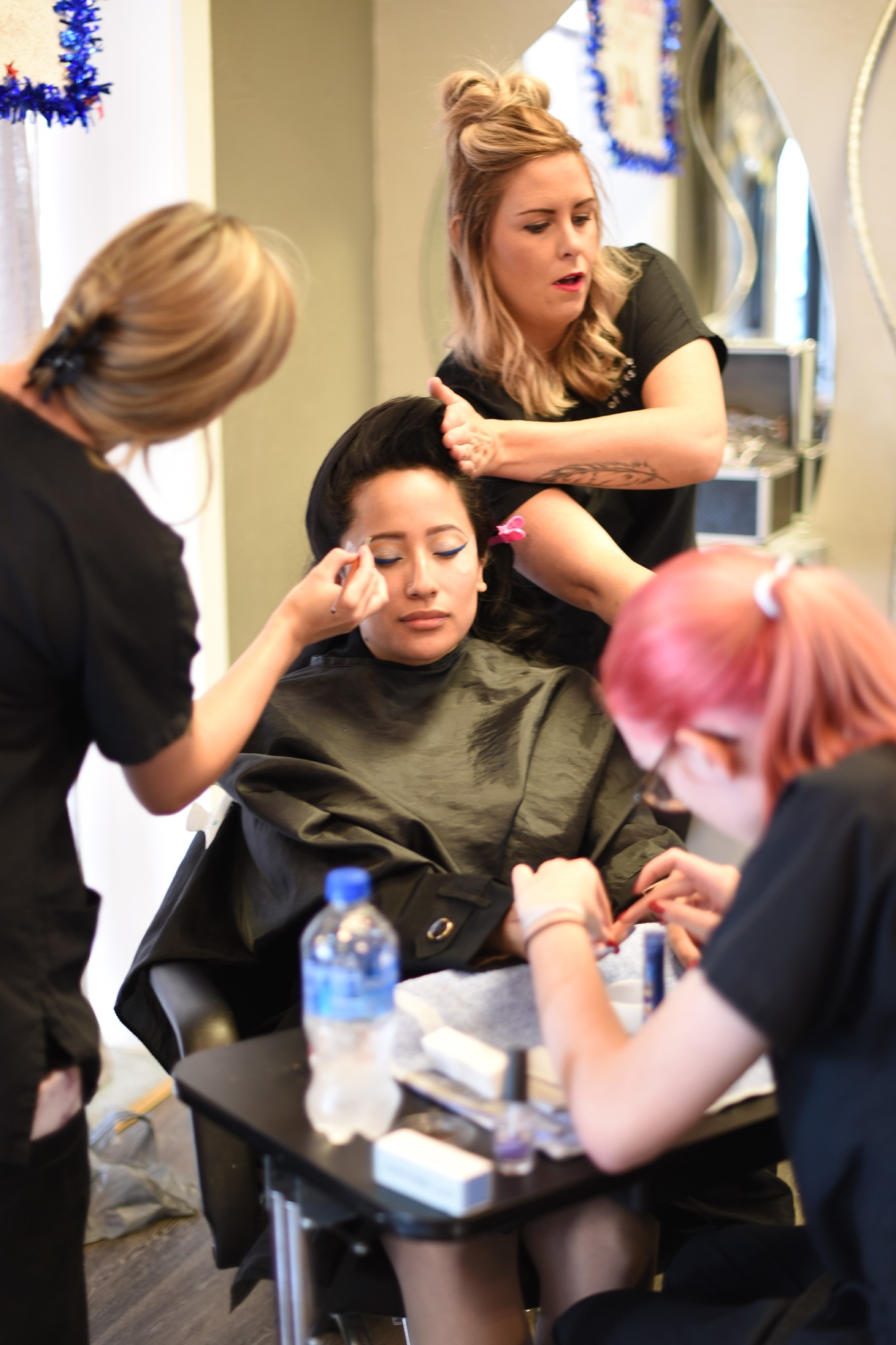 Three women cooperating to put makeup on their customer