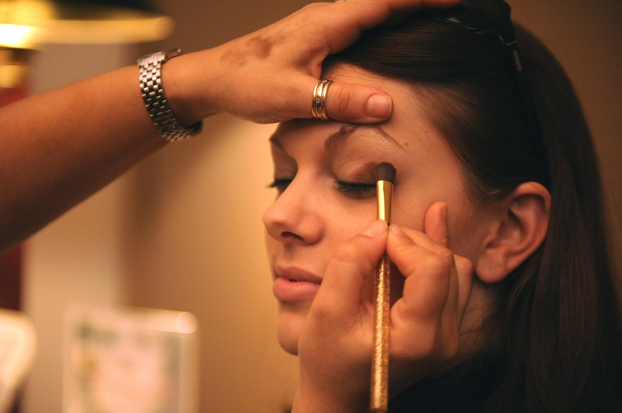 Makeup - A young beautiful woman sitting down while another woman applies mascara to her face inside a spa room